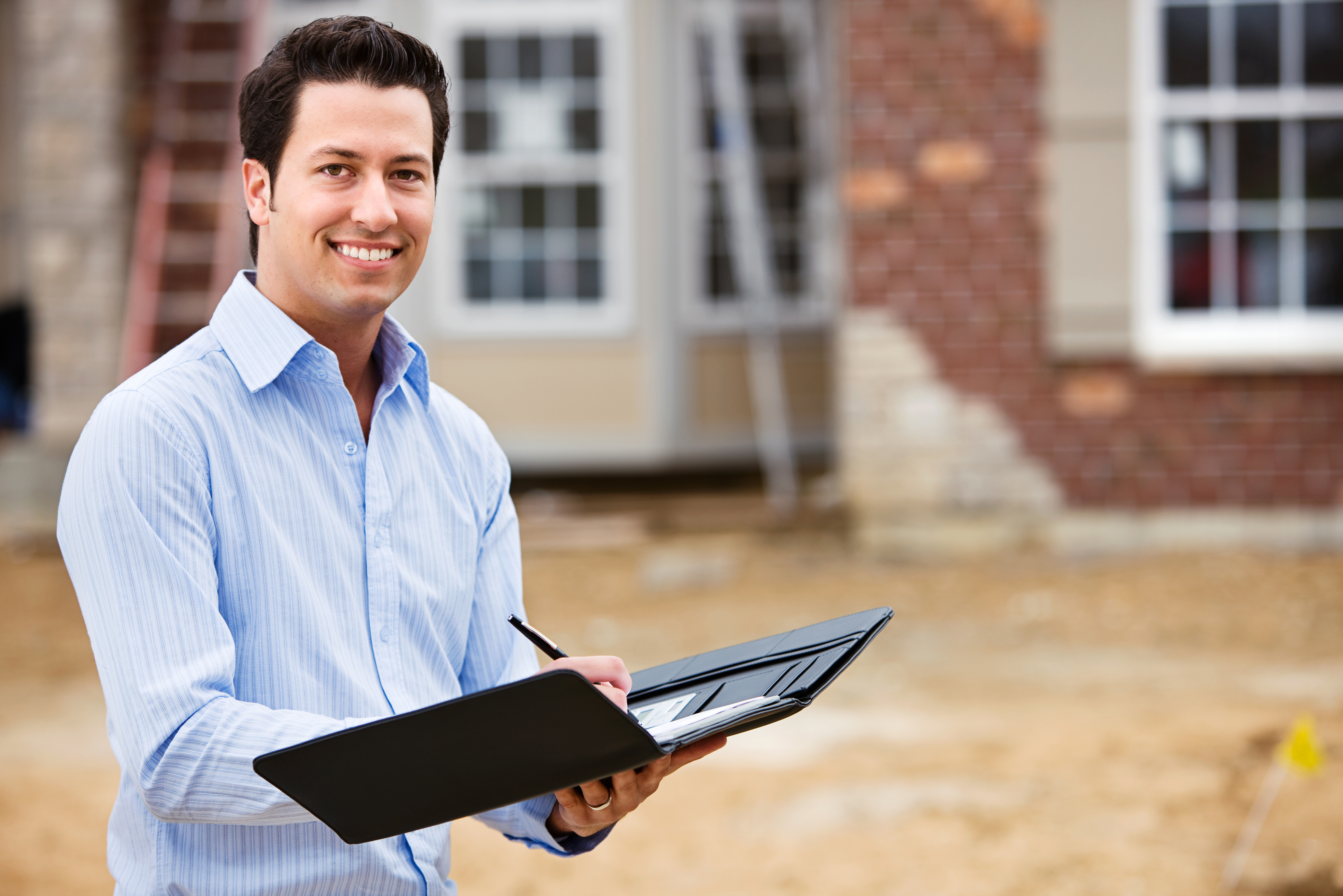 Image of a real estate agent for new construction standing in front of a construction site.