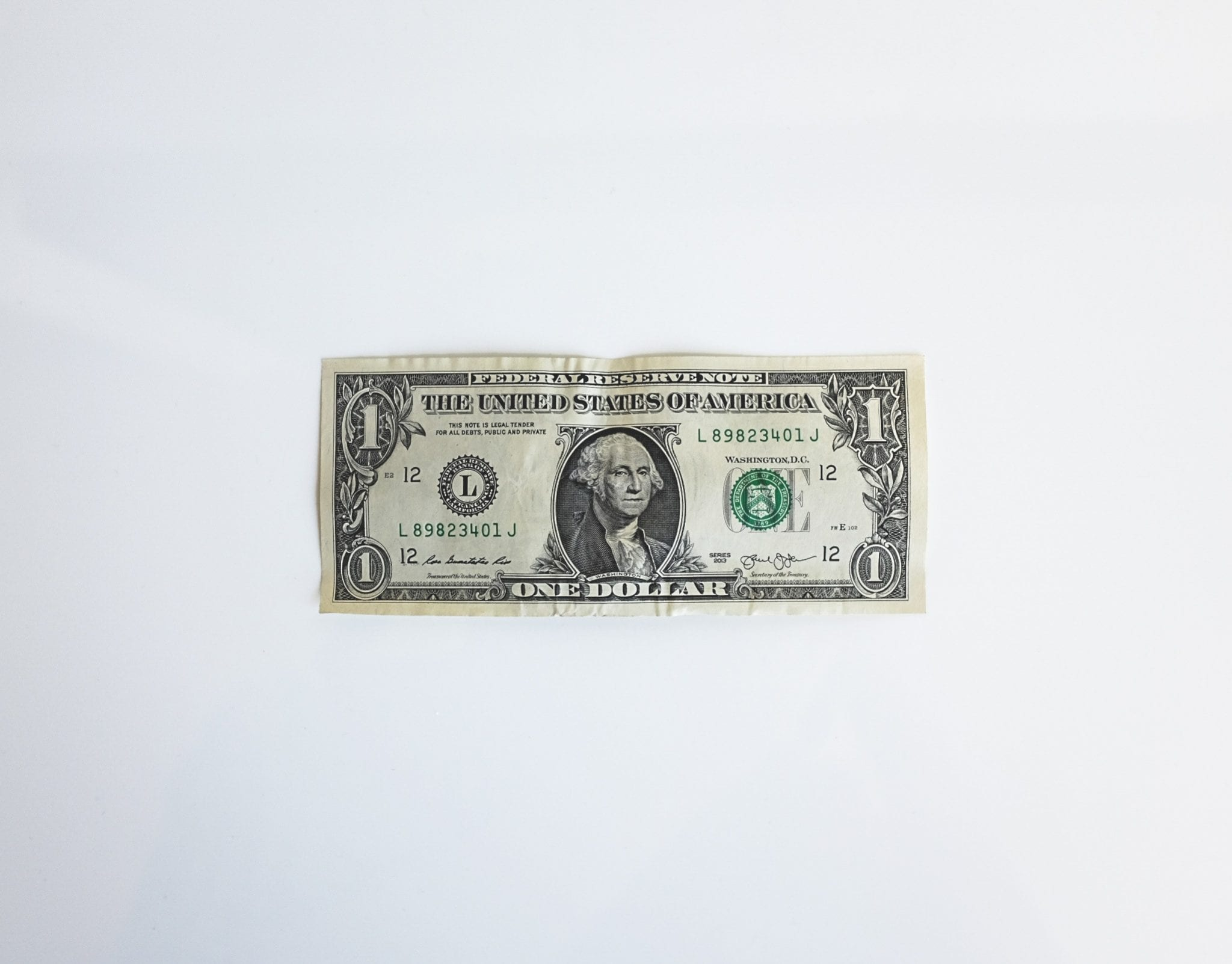 One US dollar bill on a white background to represent earnest money