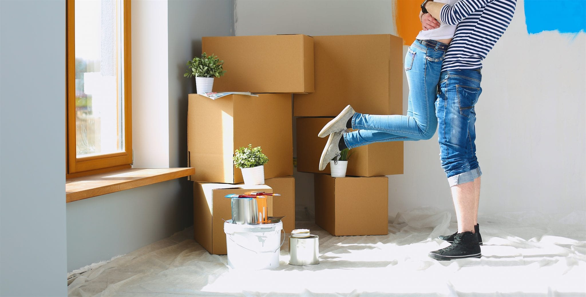 Legs of happy young couple moving into home.
