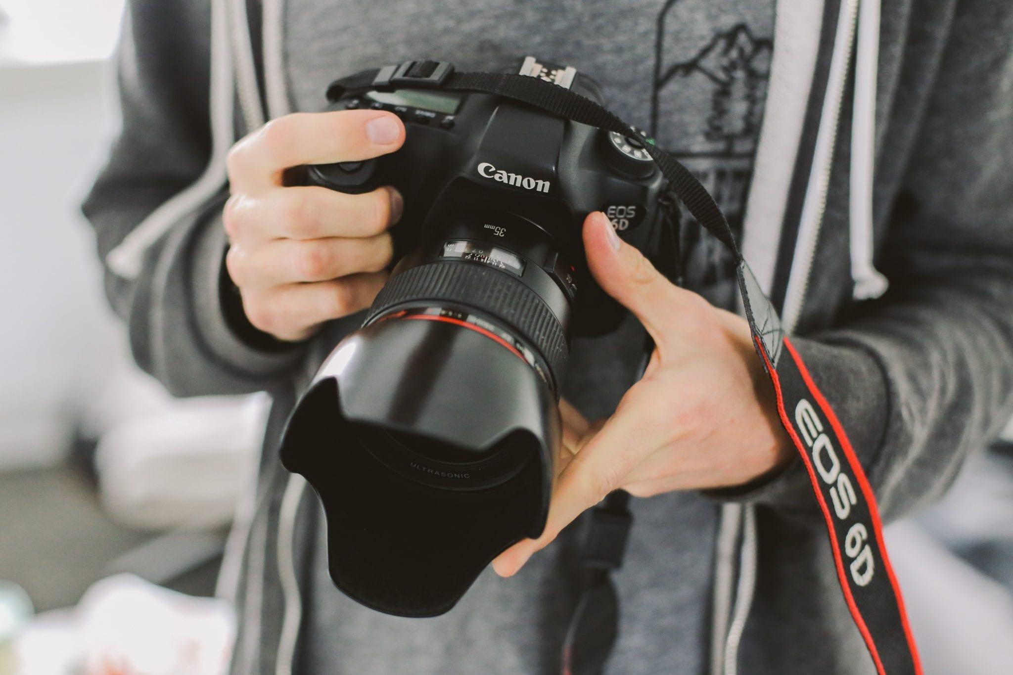Real estate photographer holding Canon camera