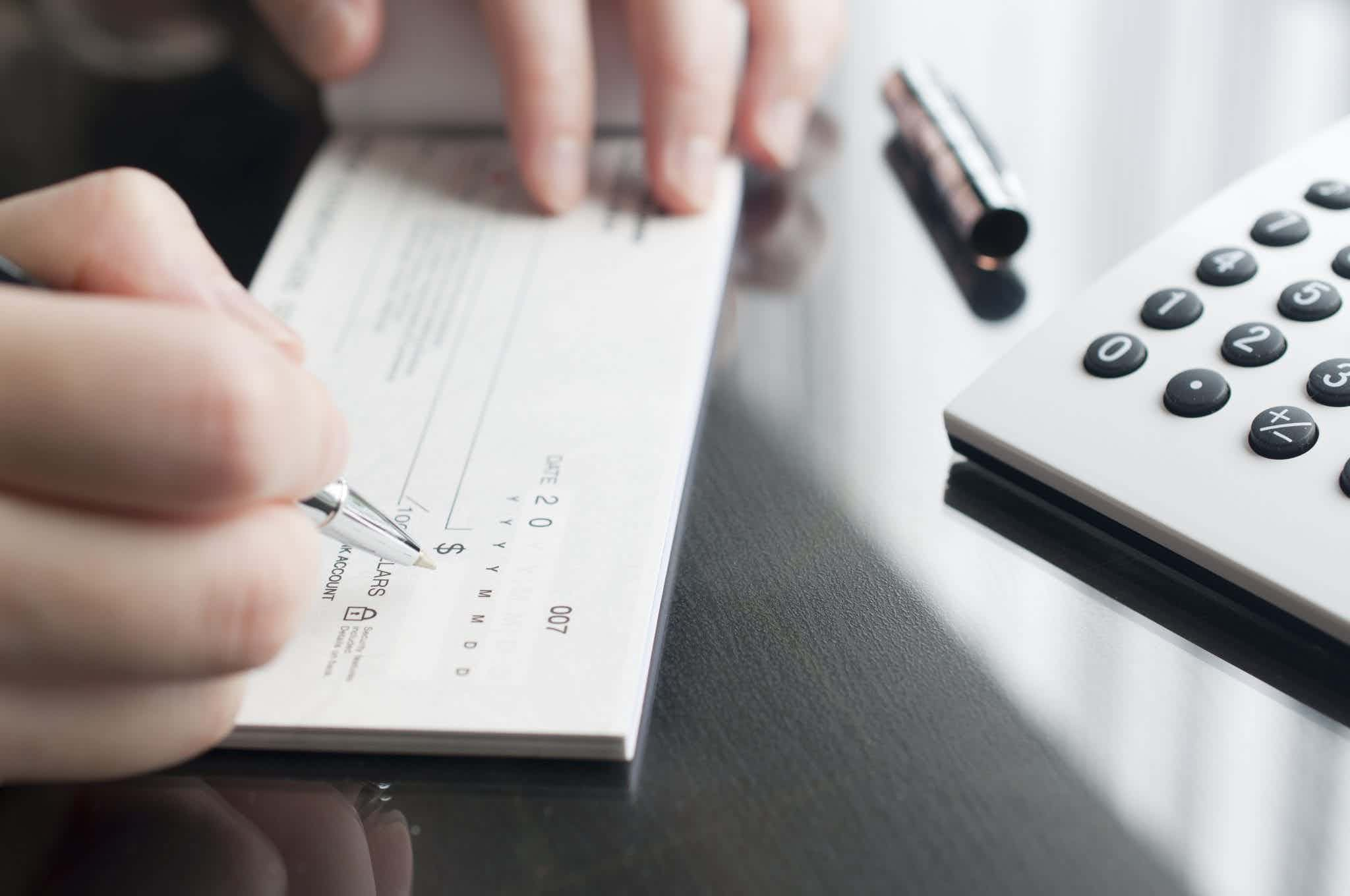 Hands of a person writing a check