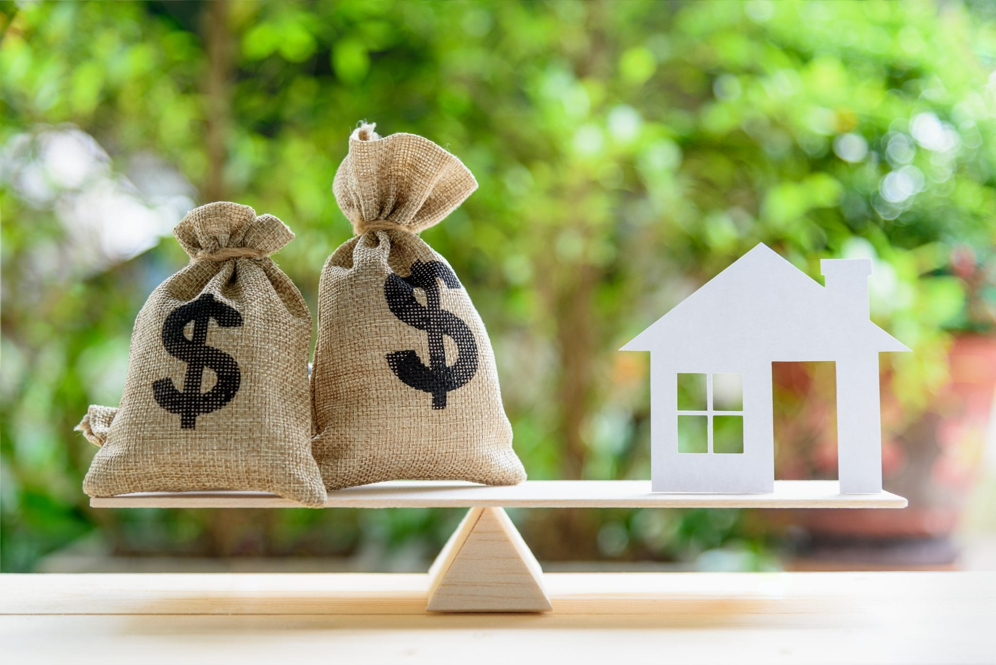 Money balanced on a scale with a house to represent home equity. Here's how to calculate equity.