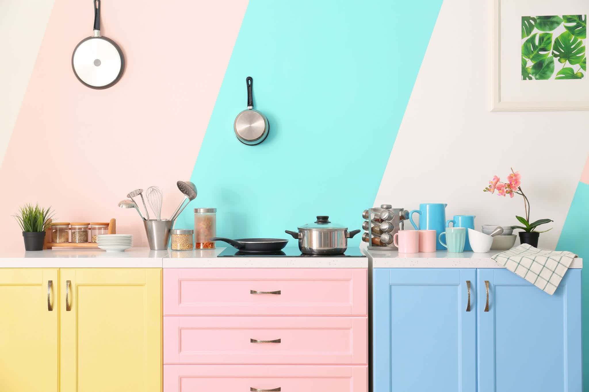 Yellow, pink, and blue kitchen cabinets with pink and blue striped walls. (Hint: the best kitchen paint colors aren't any of these!)