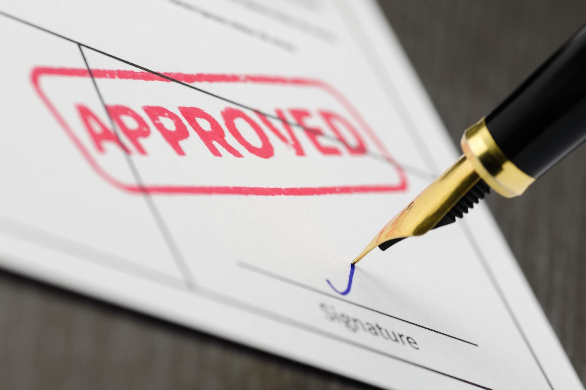 Pen signing paper confirming someone will get approved for a mortgage