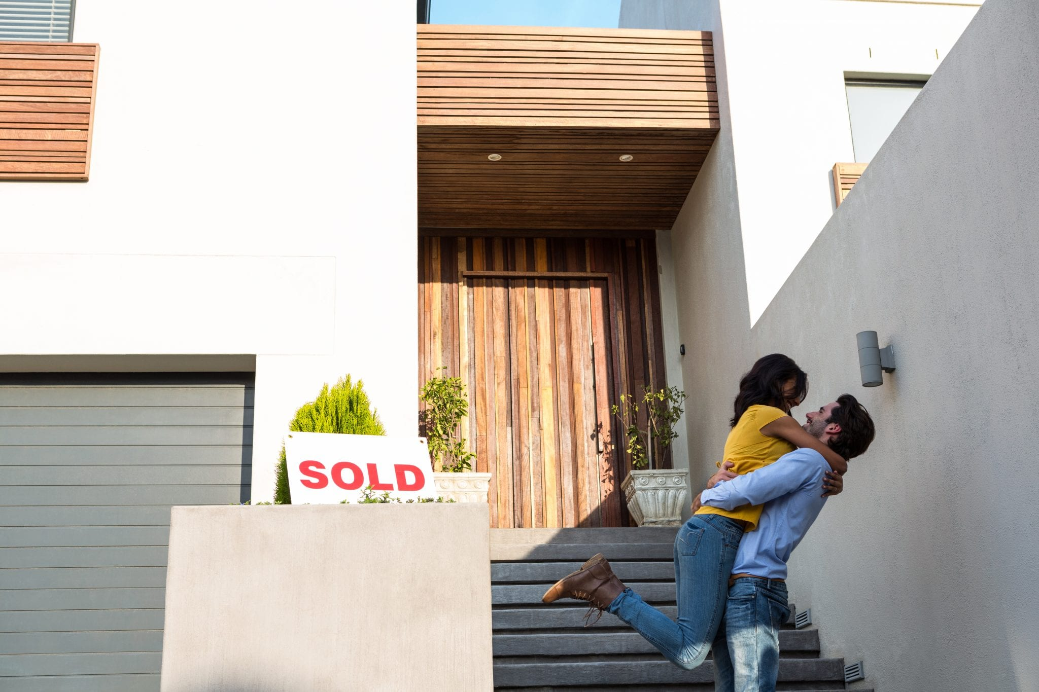 Young couple celebrates in front of their new home purchased with a first time homebuyer program