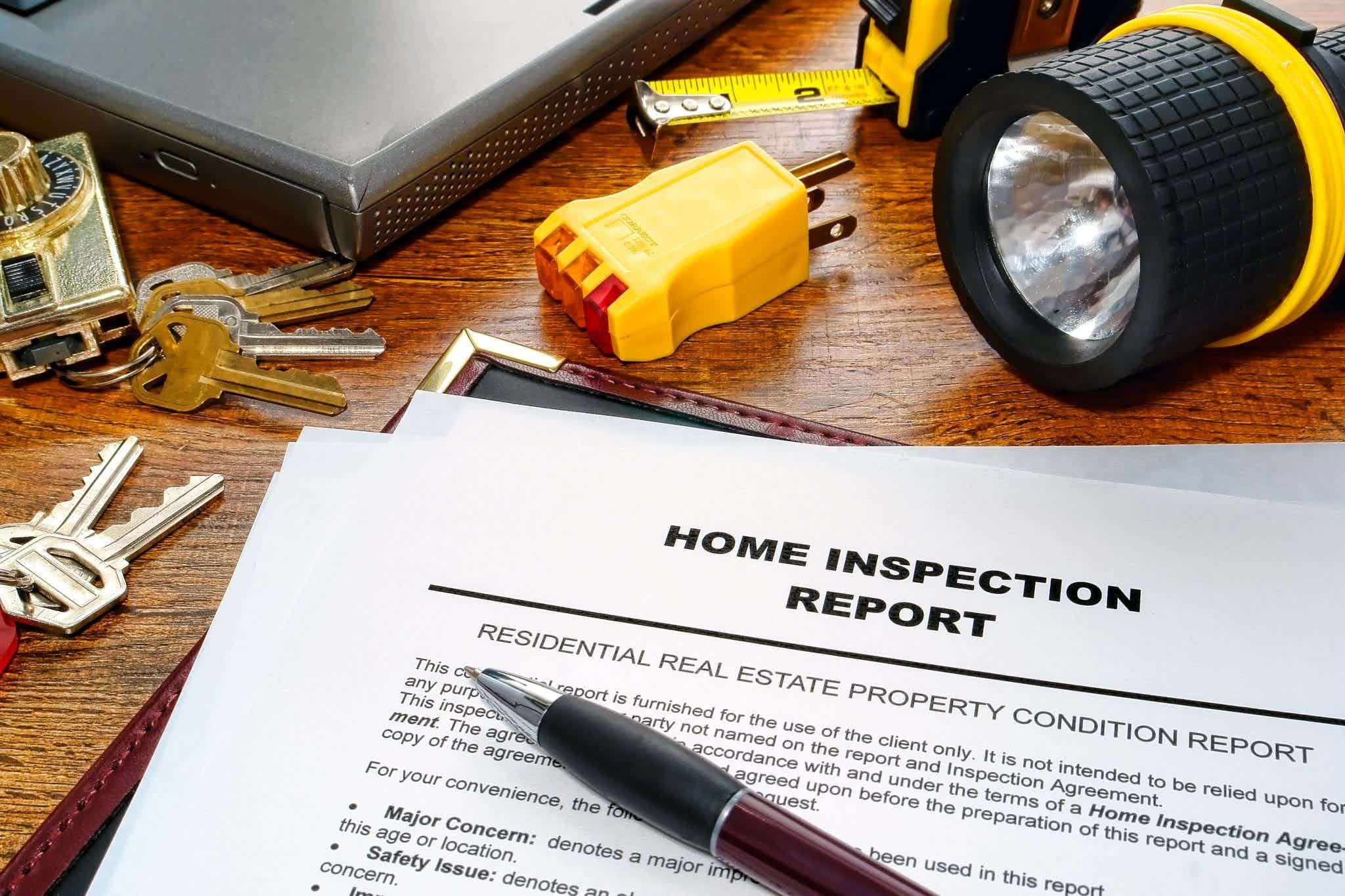 Home inspection report surrounded by pen, keys, and flashlight