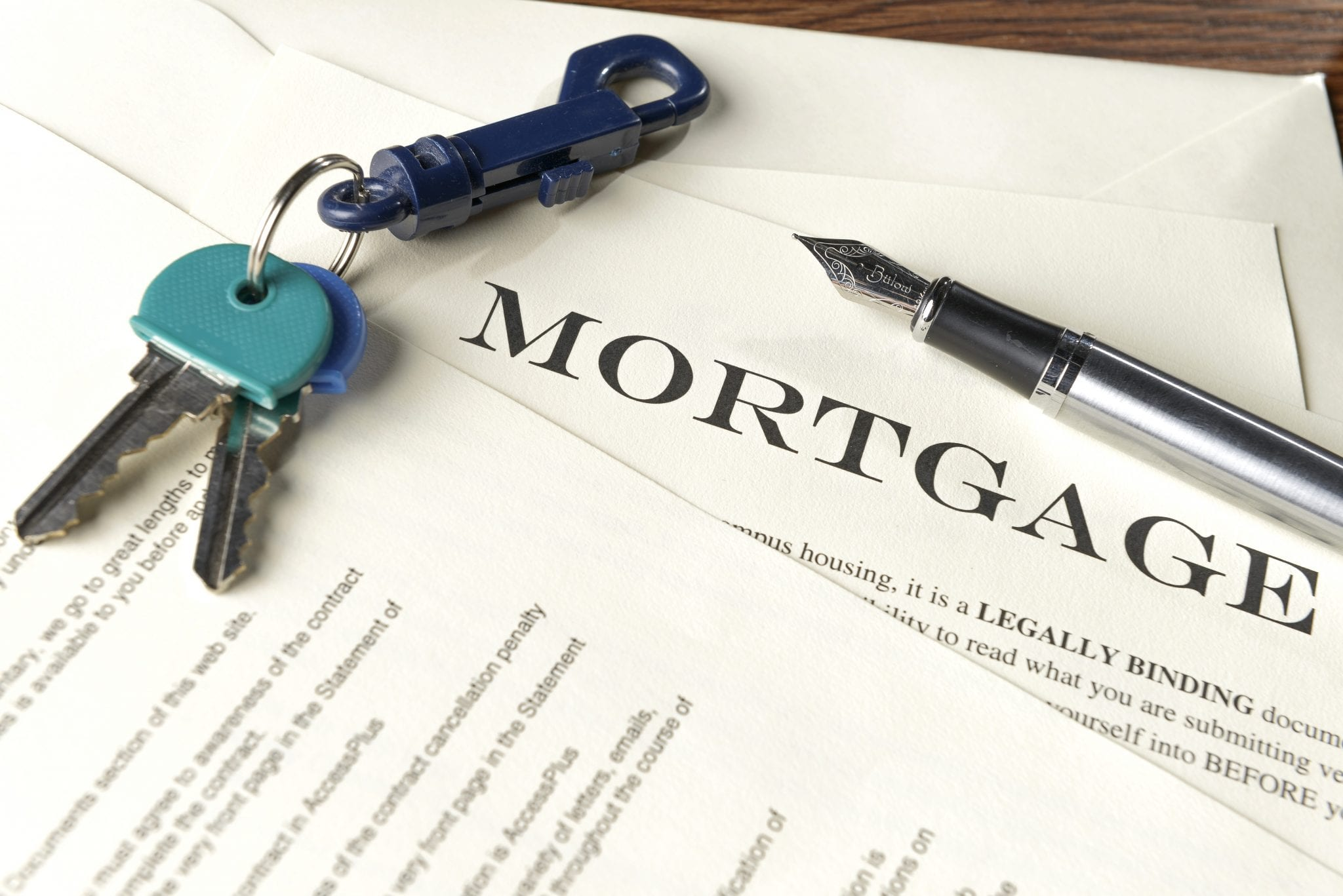 Mortgage note on table with house keys and pen.
