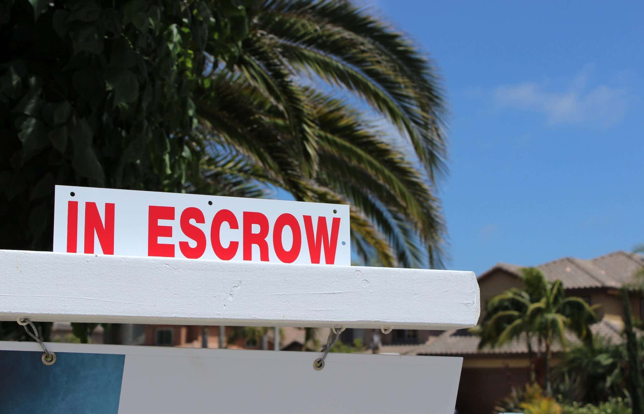 In escrow sign in front of house.